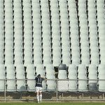 Lisa De Vanna, her back to the camera, looks dejected in front of empty seats in a football stadium.