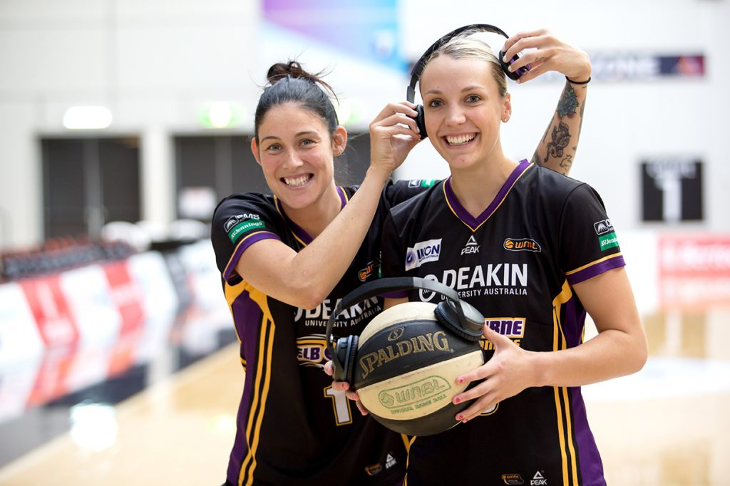 Tegan Cunnigham & Maddie Garrick from the Melbourne Boomers. They're holding earphones on a basketball.