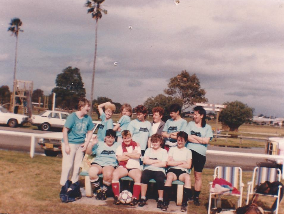 A groups of women in football kits, linked up for a team shot with a soccer ball. Photo taken circa 1986.